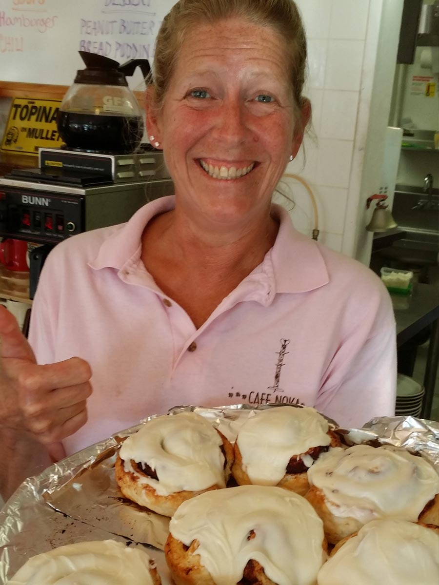 employee showing cinnamon rolls